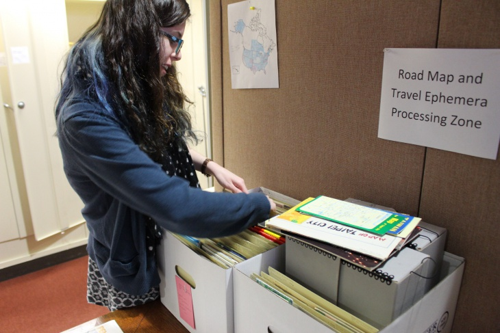"Processing Assistant Emily Richardson at work in the ""Road Map and Travel Ephemera Processing Zone"""