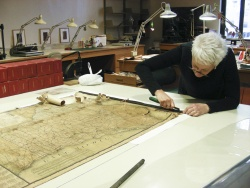 Collections conservator Barbara Korbel working on a map.